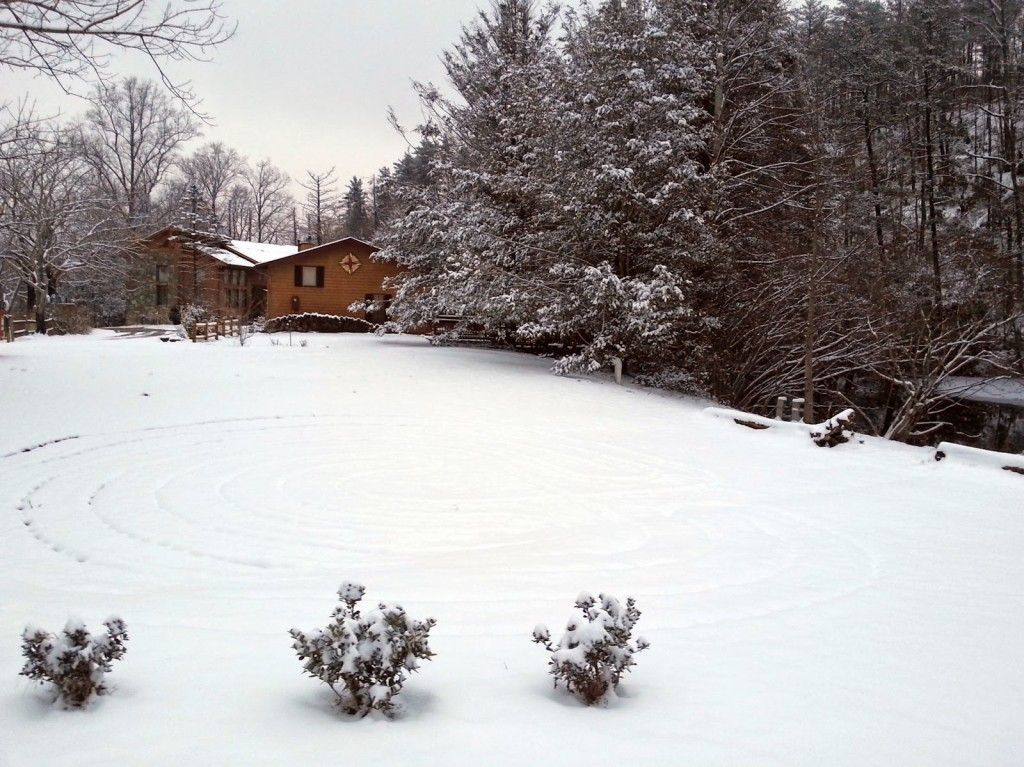 Walking labyrinth outlined under snow with buildings and trees in the background