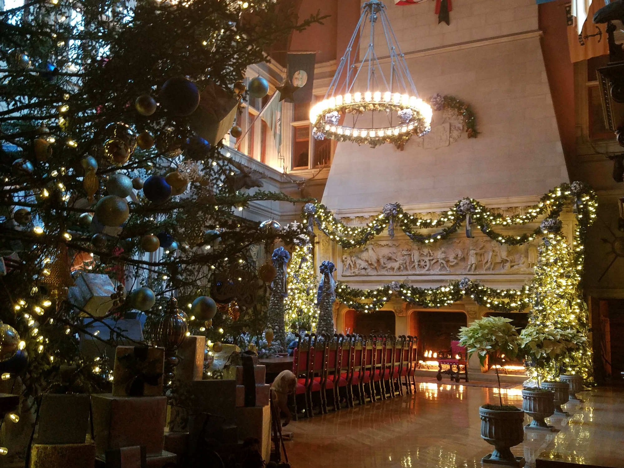 Christmas decorations in a dining hall several stories tall with three connected stone fireplaces on one wall