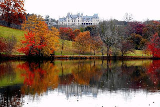 French style chateau on a hill in the fall with a large pond in front of it