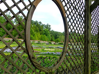 Wood lattice with oval cutout looking out on a colorful garden
