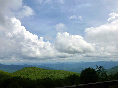 White clouds in the sky above green mountain ridges