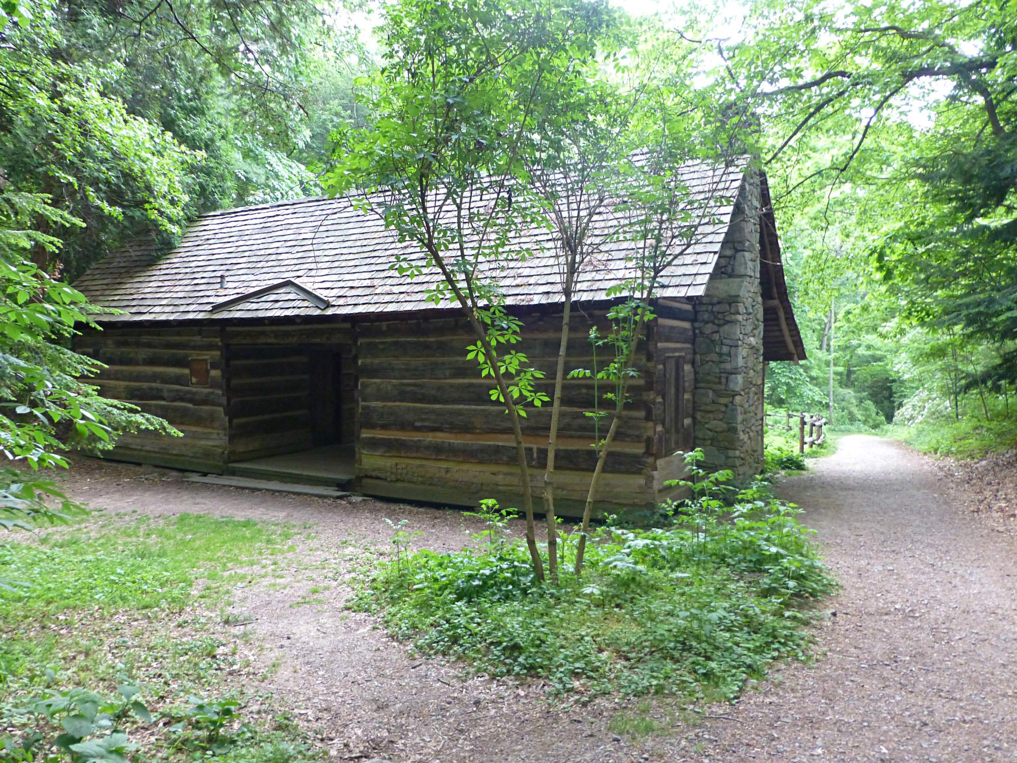 Single story log cabin with a wide dirt path running along side it in a sunny park like setting with several trees
