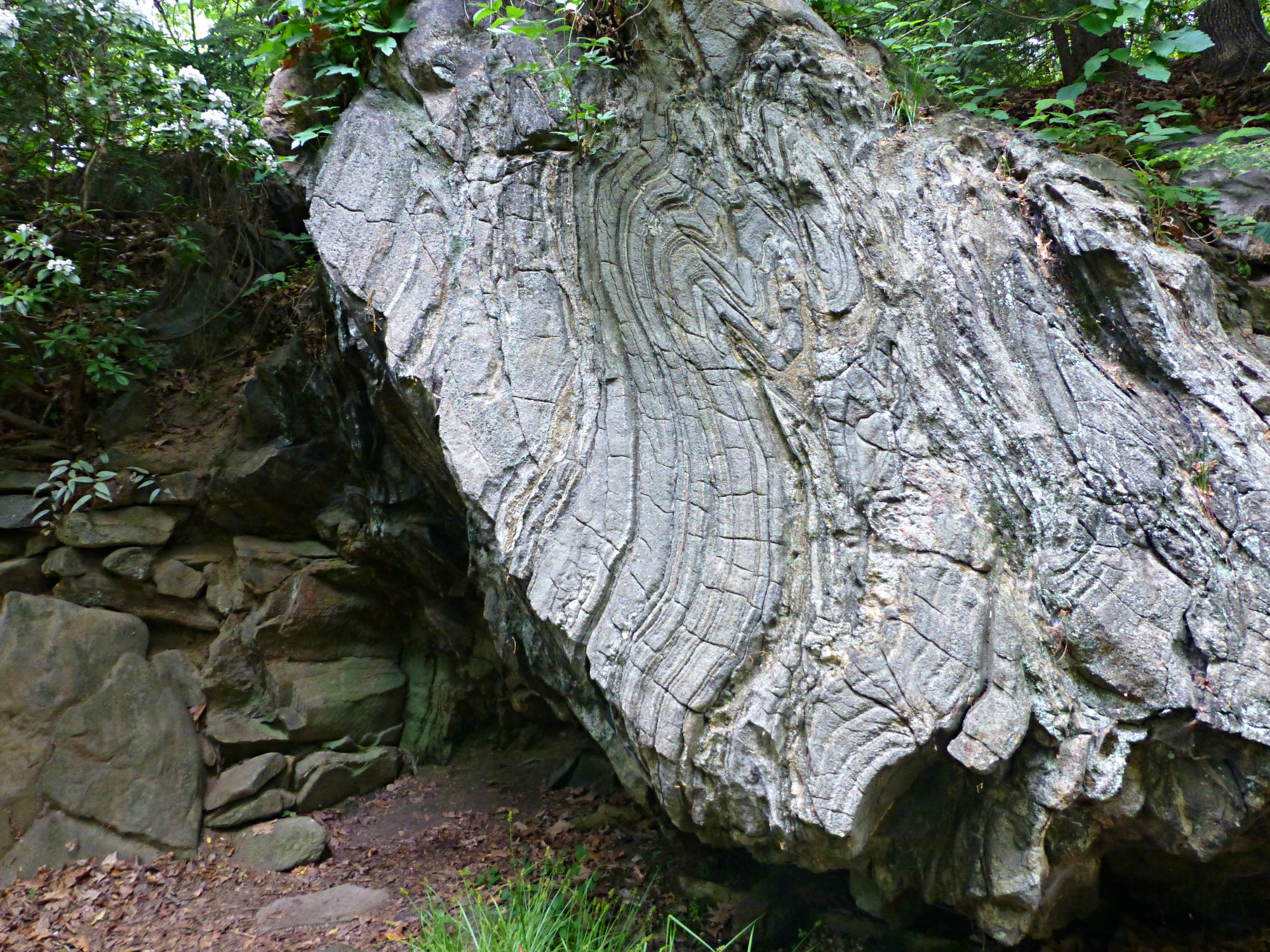 Large vertical rock formation with several grooves in the rock and other stones nearby