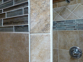Shower walls with beige tile and blue glass tile accents