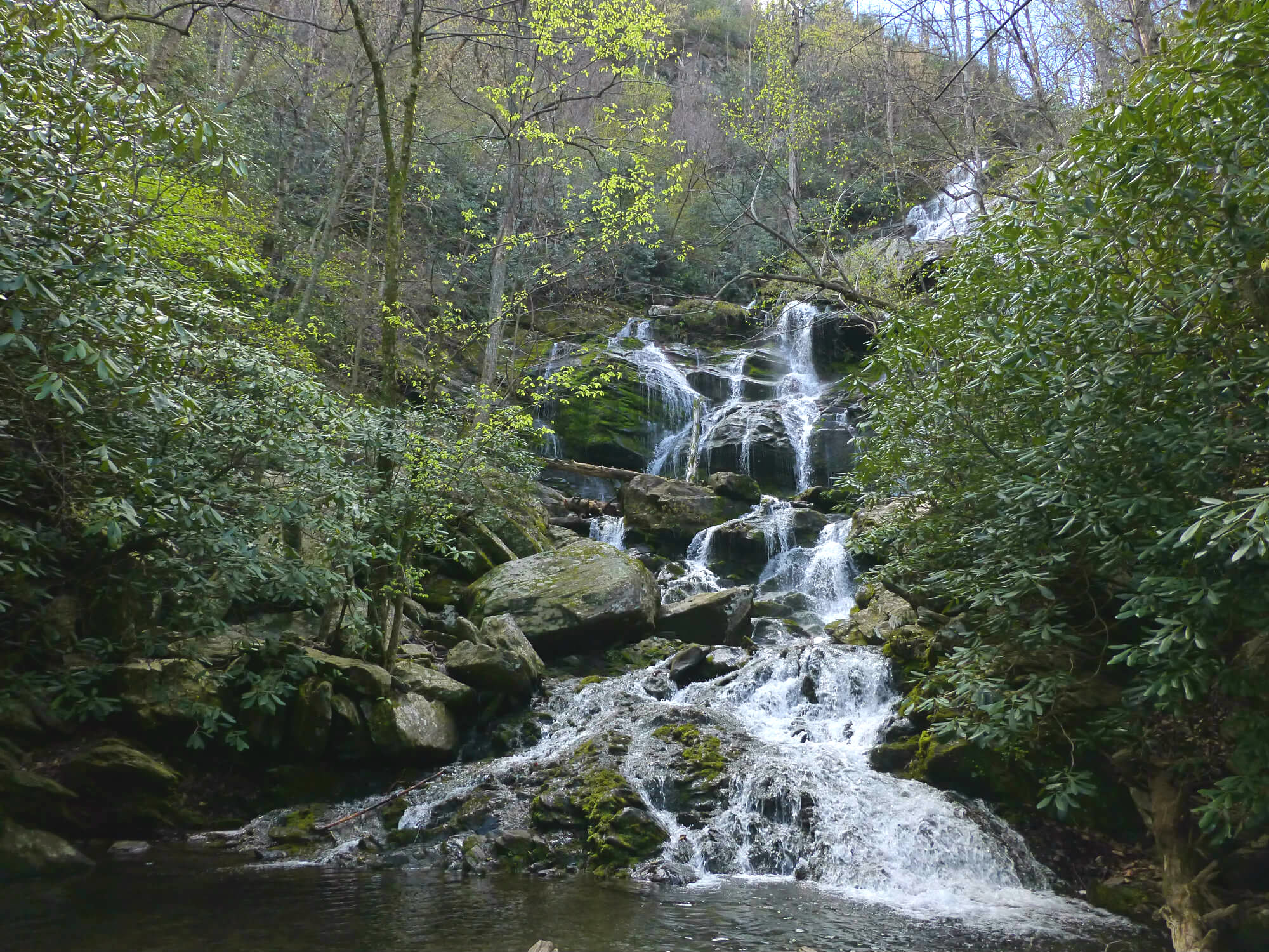 Water cascading down several large boulders with trees and other foliage around it