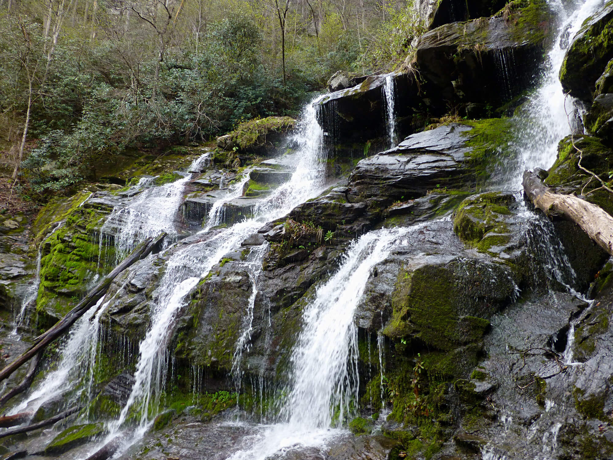 Portion of a waterfall with water spilling over several moss-covered boulders
