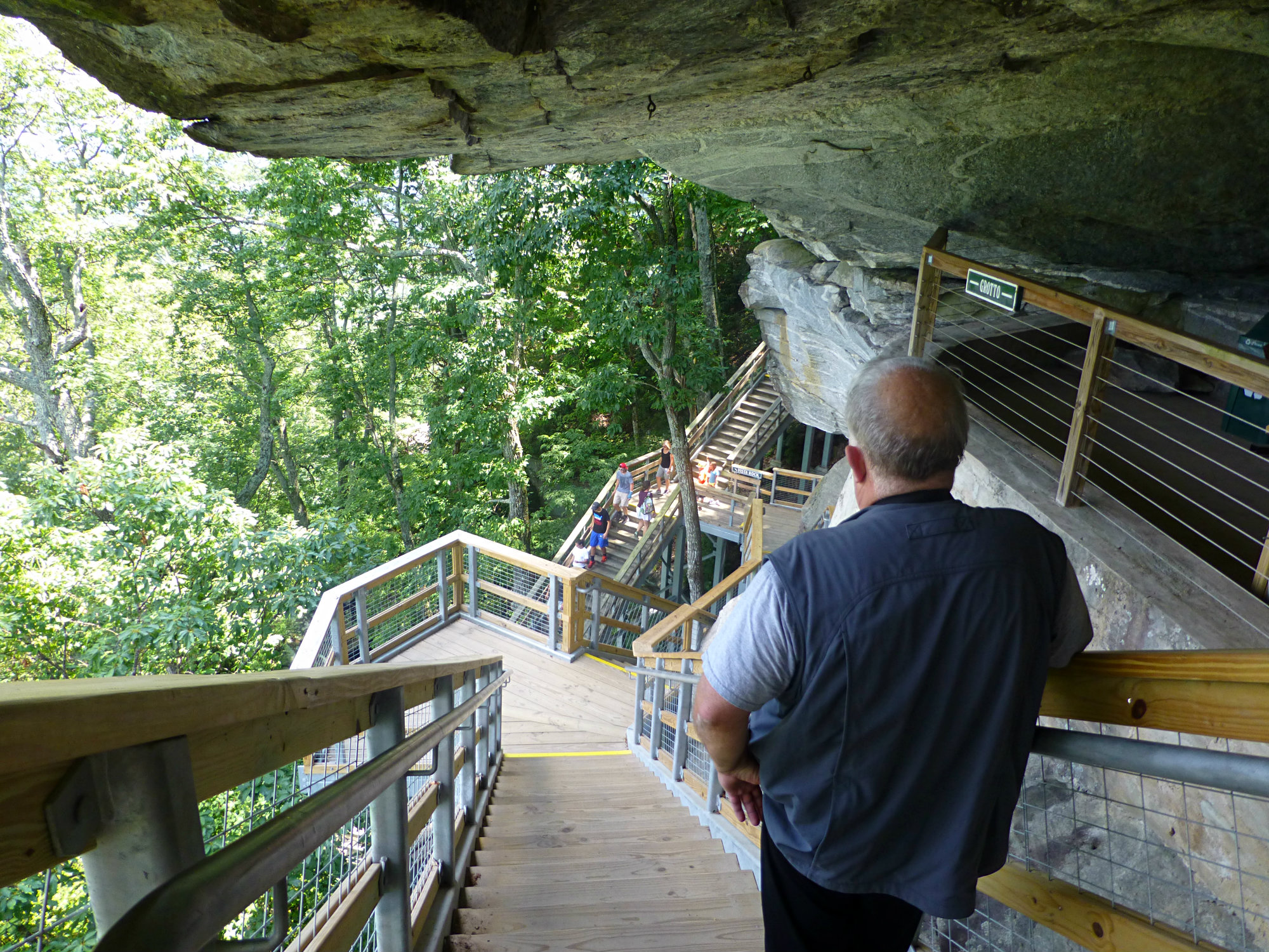 Man with t-shirt and blue hiking vest standing on stairs leading past a cut in a large boulder