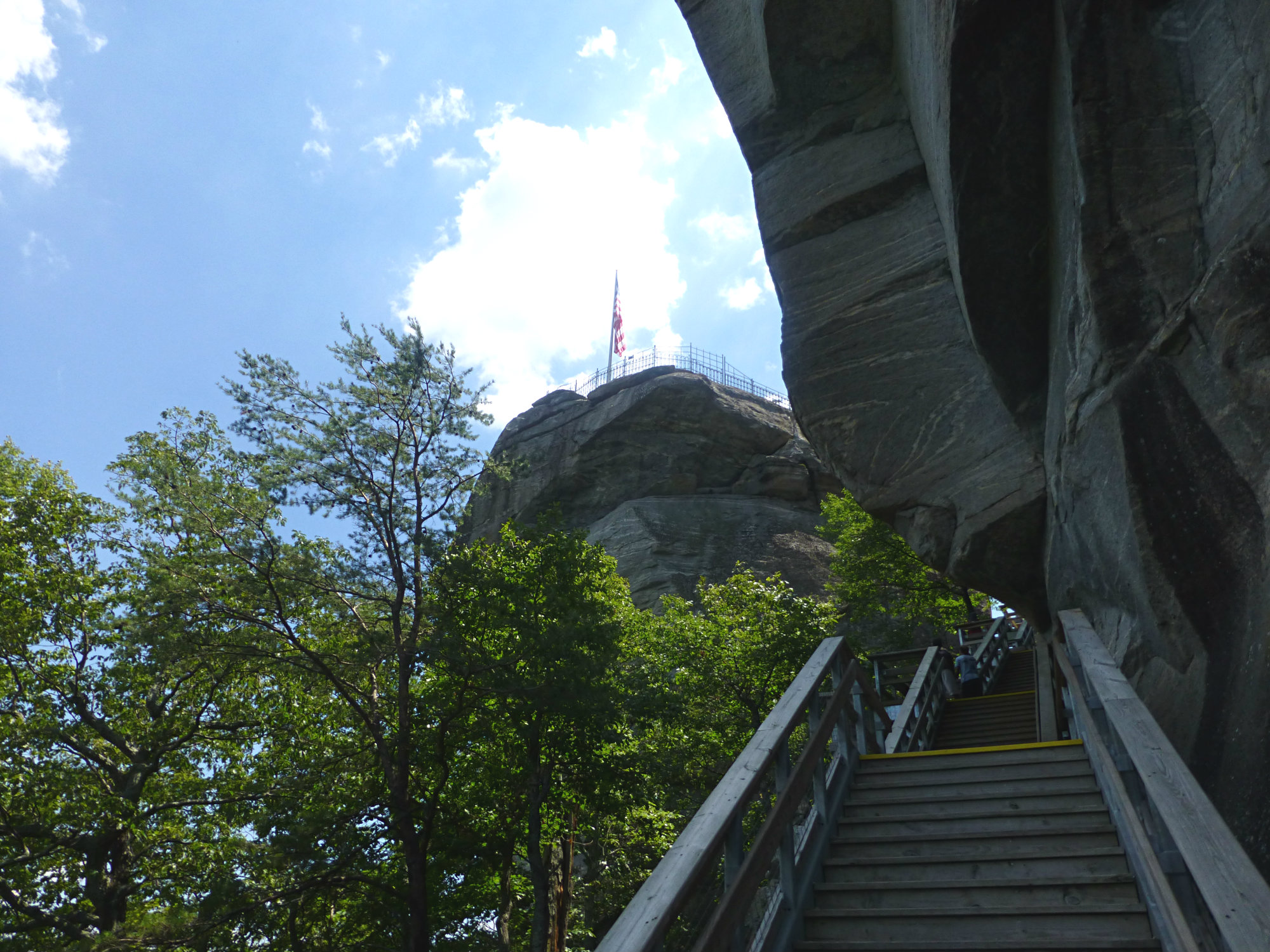 Sturdy wooden stairs leading along a granite boulder to the top of a granite rock with a flag flying on it