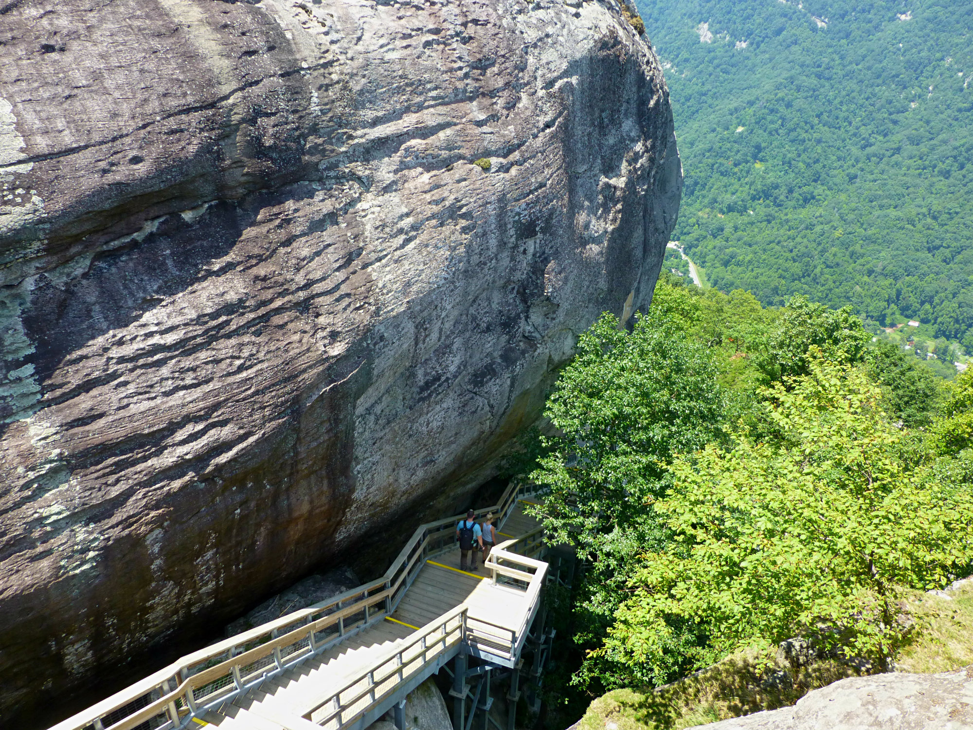 View looking down on a gigantic boulder with people walking down stairs next to it