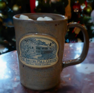 Sand colored Inn on Mill Creek logo mug filled with hot cocoa and marshmallows