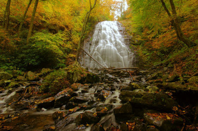 Beautiful cascading waterfall that ends in a rocky creek in the woods