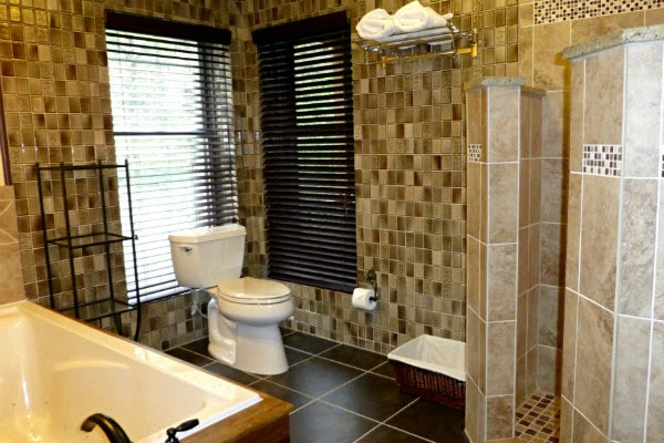 Bathroom with dark tiled floor, large bathtub and white toilet