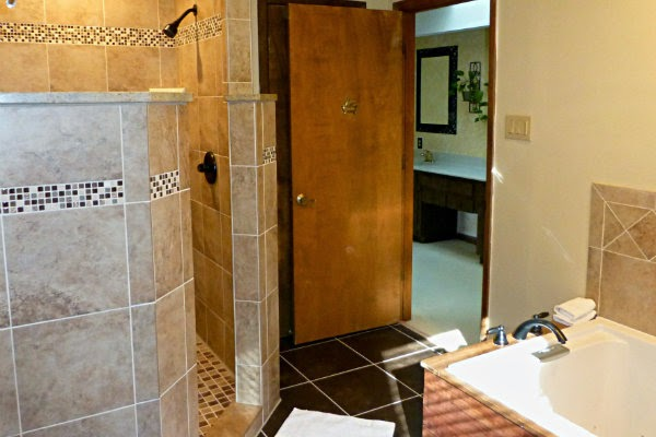 Bathroom showing walk-in tile shower and corner of tub
