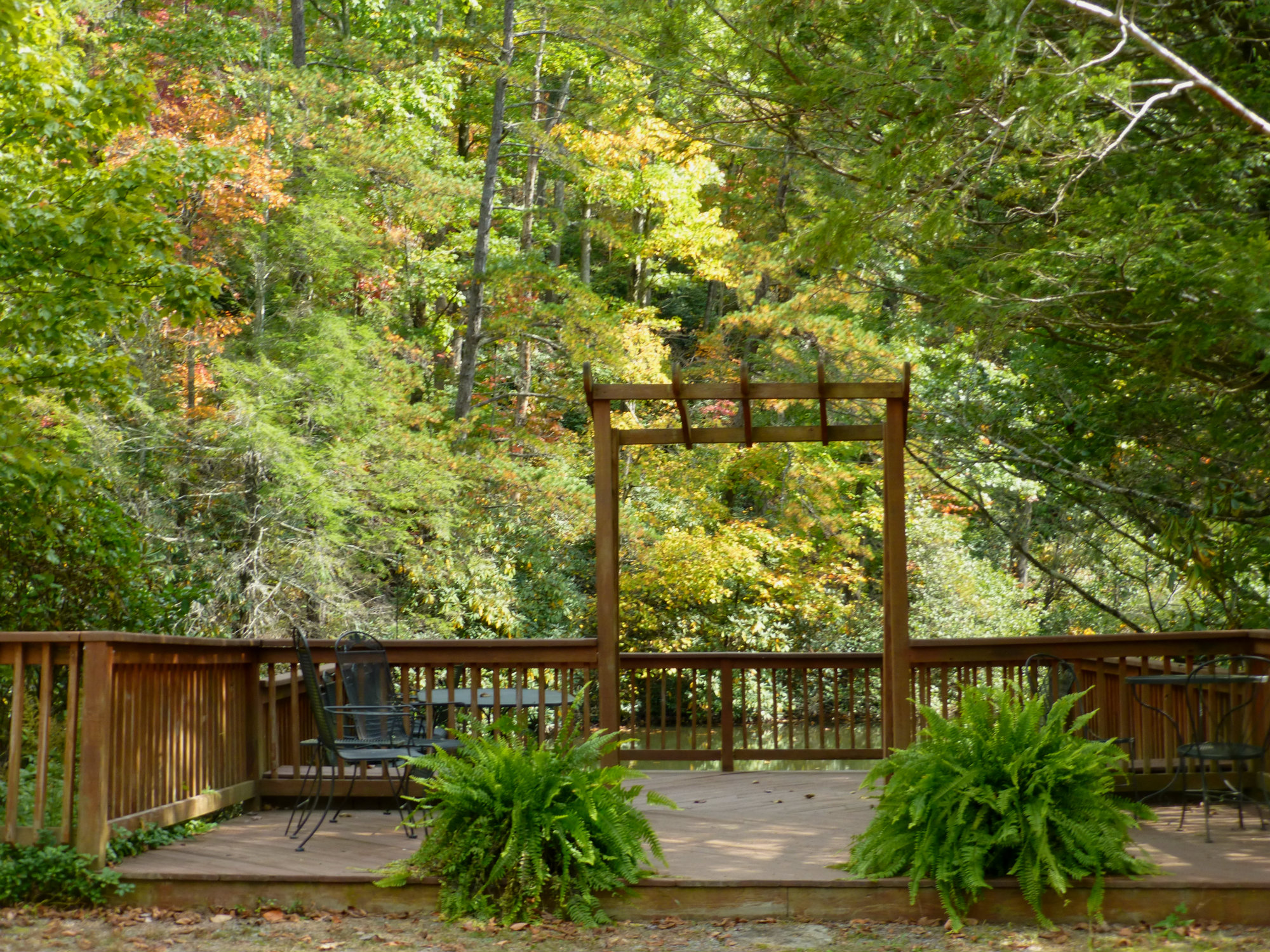 Deck with a square archway and railing with a backdrop of trees