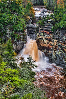 High volume waterfall after a rainfall with muddy water and a raging river