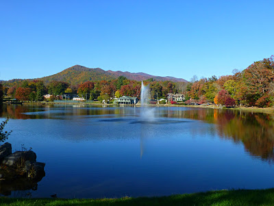 Large blue lake with fall colors on mountains behind it under a blue sky