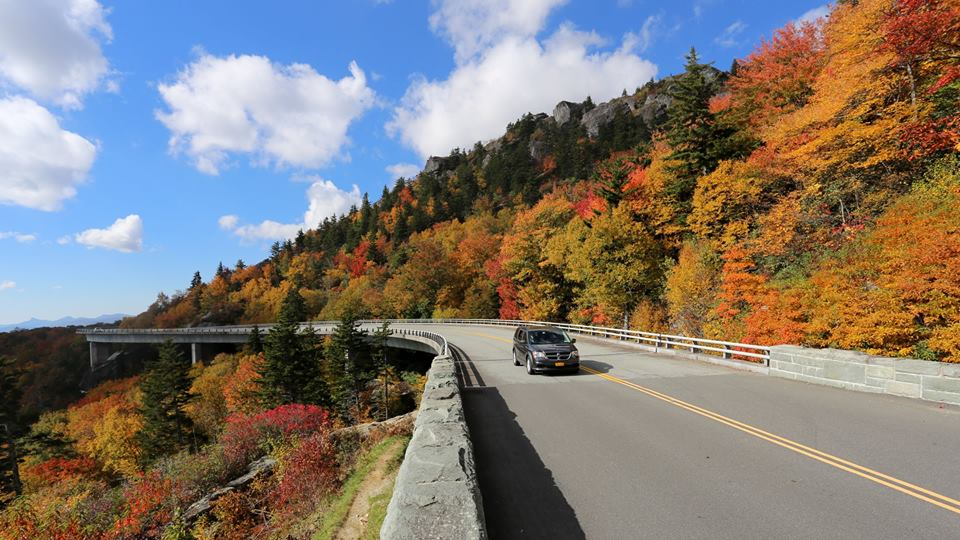Car driving on a road that curves around a tree-covered slope with fall color all around