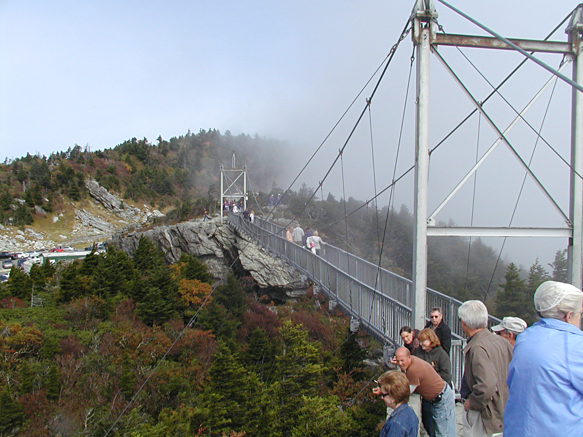 Long suspension bridge leading to a rugged hillside covered in trees