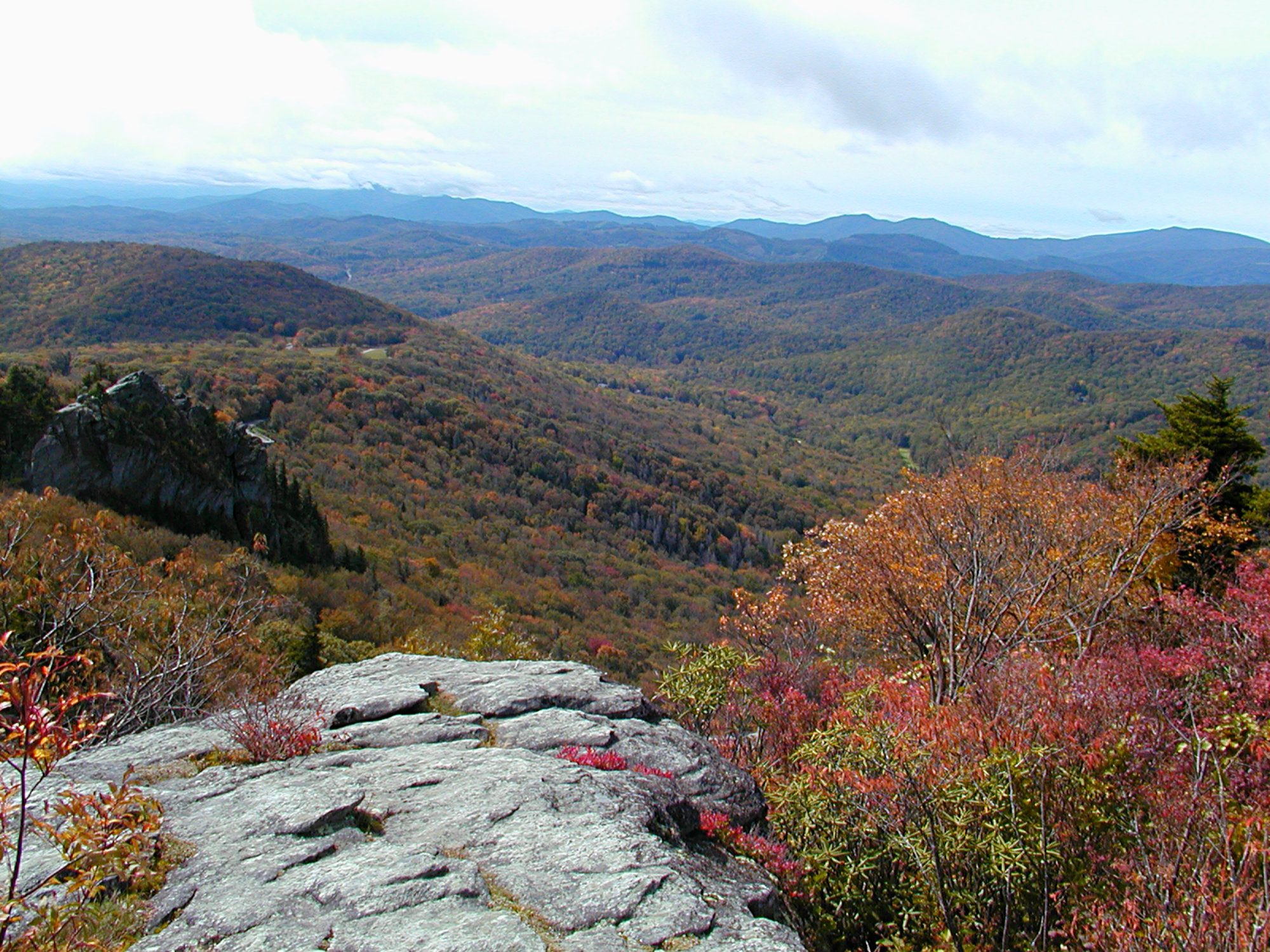 View of tree covered valley and mountains from a rocky ledge