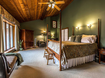 Room with forest green walls and tall windows and large four poster bed