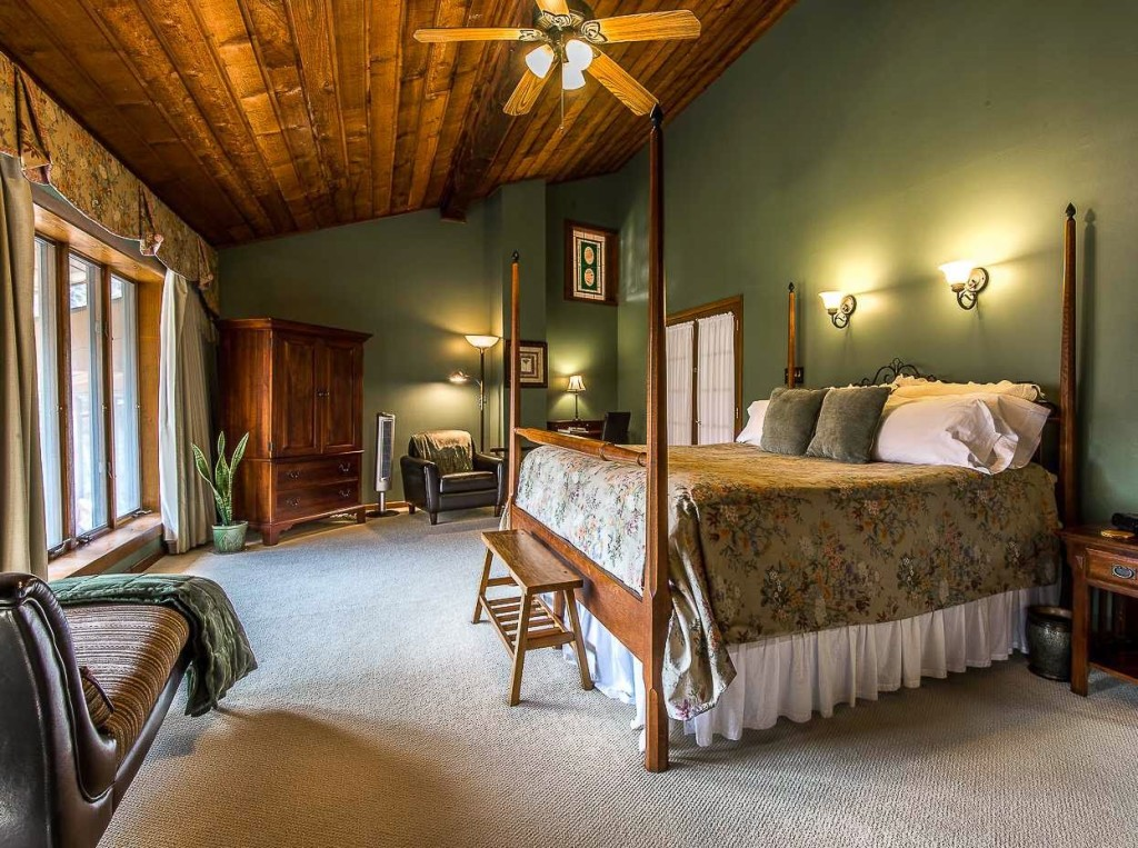 Room with cedar plank ceiling, floor-to-ceiling windows and large four poster bed with floral bedspread
