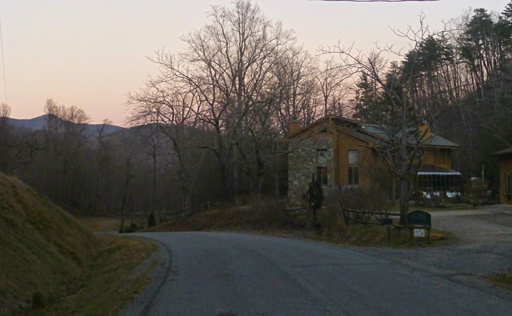 Road leading by a large wood and stone home at sunrise with mountains in the distance