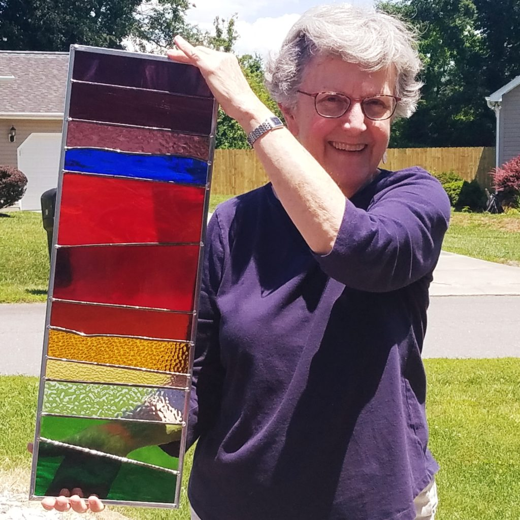 Woman smiling and holding multi-colored vertical stained glass piece of art