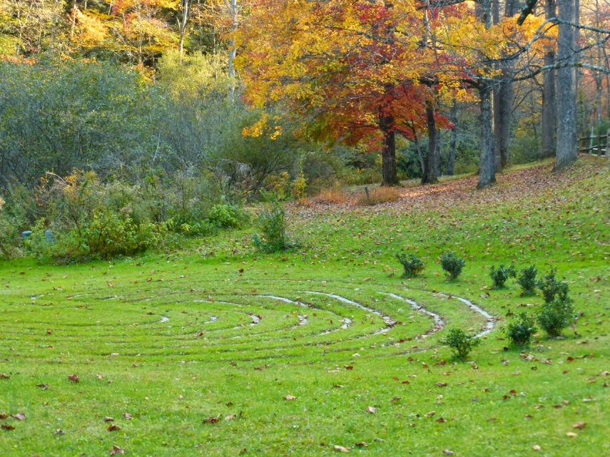 Lawn with trees in fall colors in the background and a walking labyrinth in the foreground