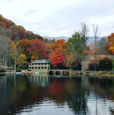 Fall color mountain backdrop and building with several stone columns along a lake