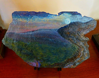 Painting on rugged slate tile of moon rising over green and blue mountain peaks