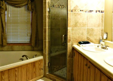 Bathroom with large tub on one side, tile shower in the middle and sinks on the other side