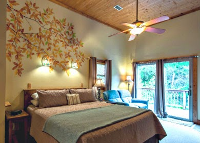 Bedroom with mural of leaves painted on wall above bed and glass doors showing foliage outside