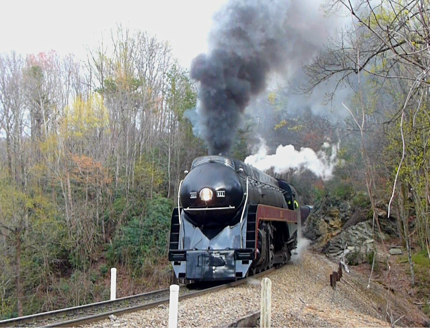 Large bullet-shaped steam locomotive traveling over train tracks in a wooded area
