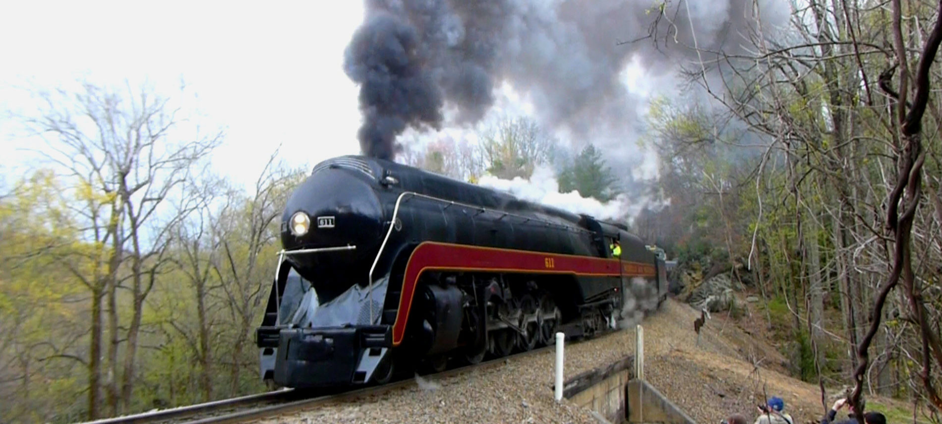 Large train engine with steam coming out of the top as it goes by on railroad tracks