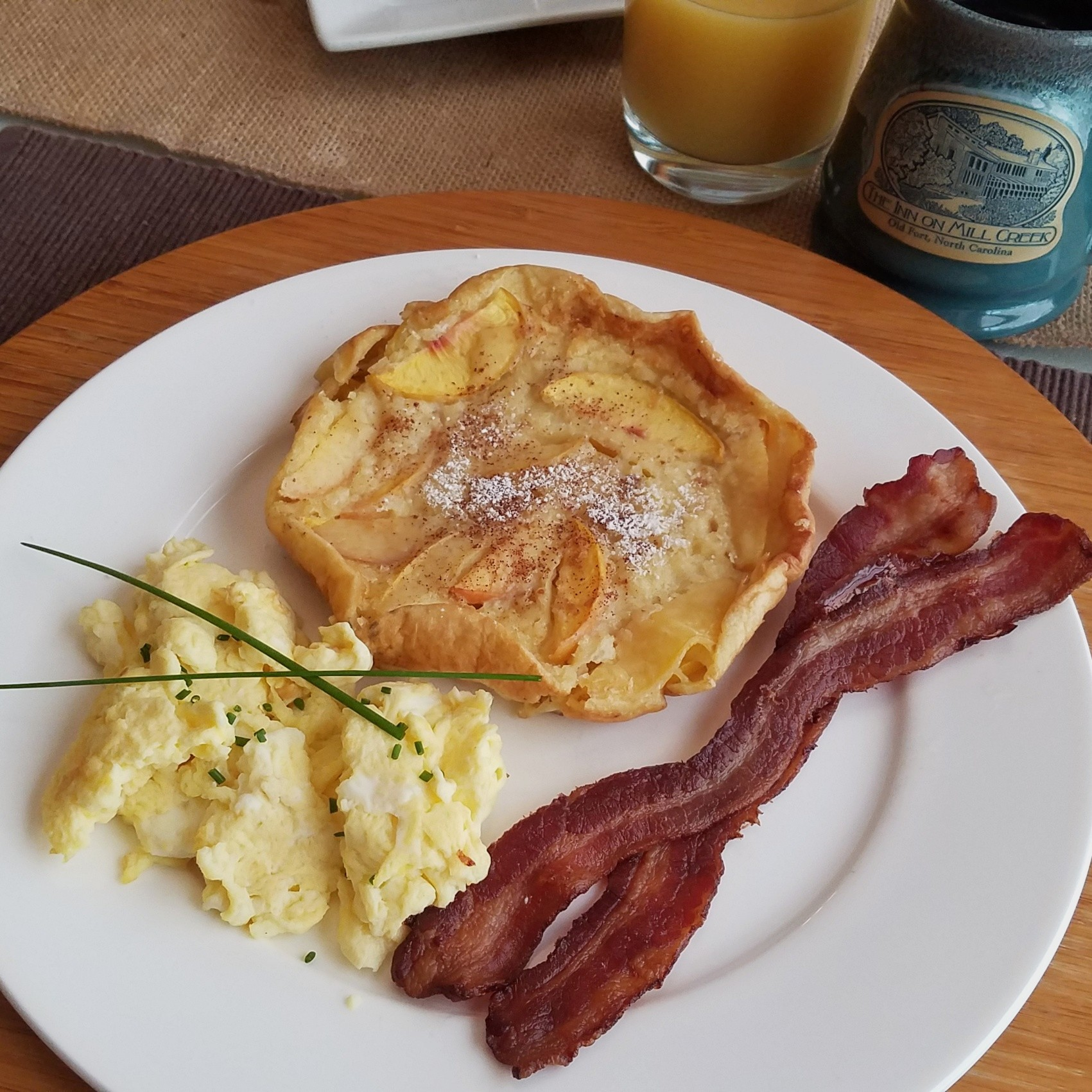 Breakfast plated with peach dutch baby pancake, scrambled eggs and bacon along with coffee in a mug and orange juice