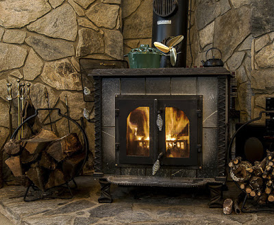 Crackling fire in wood stove with stone hearth