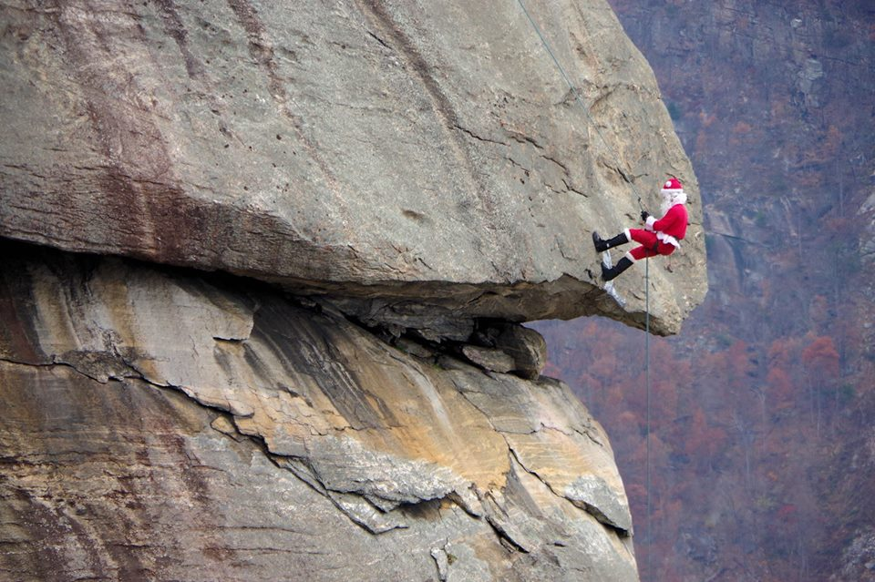 Person dressed as Santa rappelling down granite rock