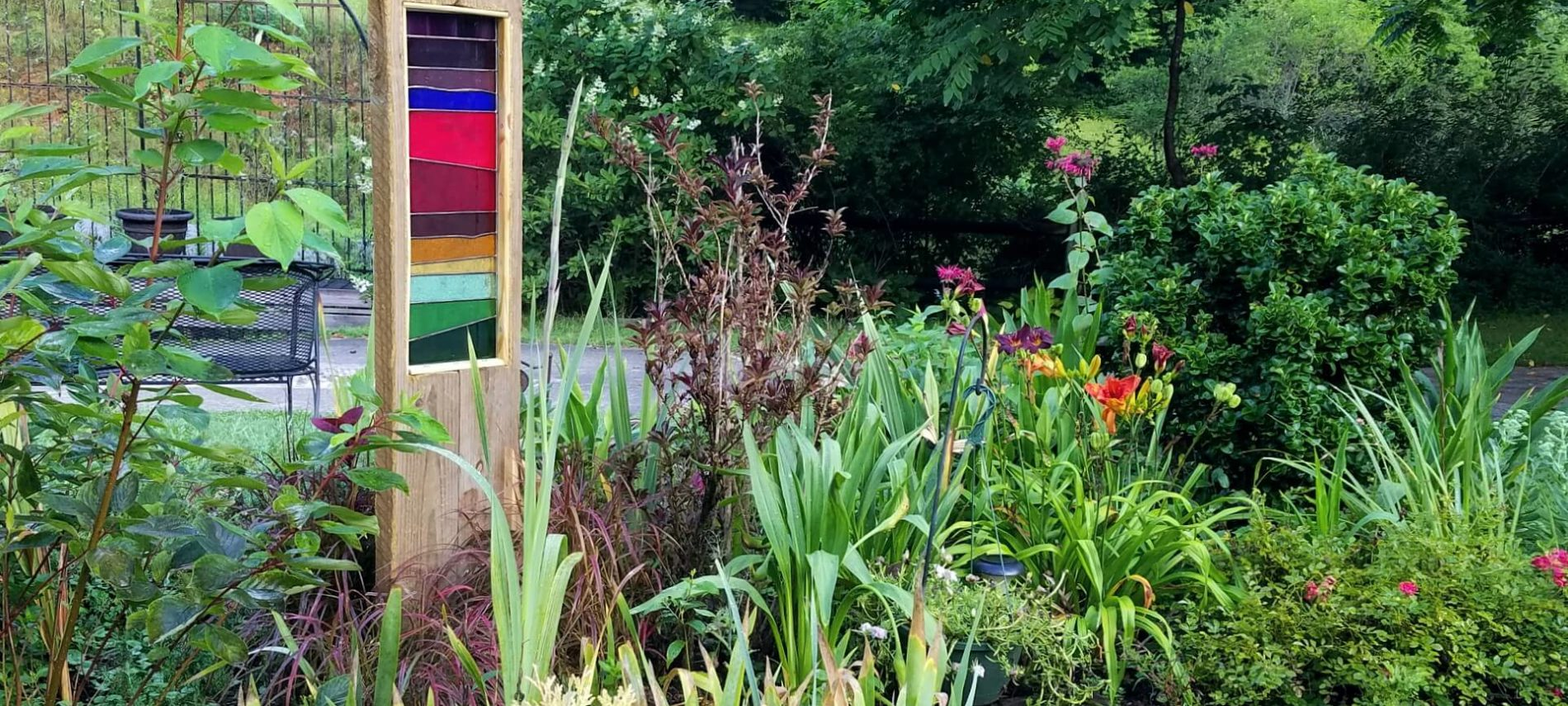 Multi-colored stained glass framed in wood in a garden
