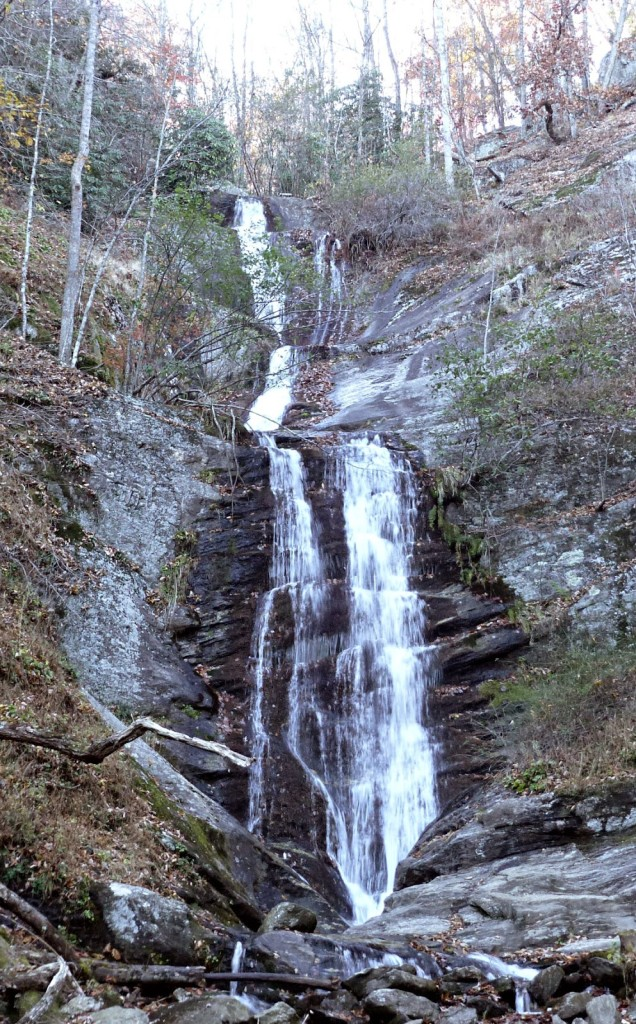 Tall waterfall cascading down slate rock surrounded by bare trees and foliage