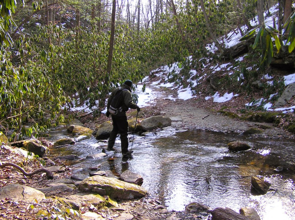 Man in winter gear with hiking pole beginning to step through rocky stream in a snowy landscape