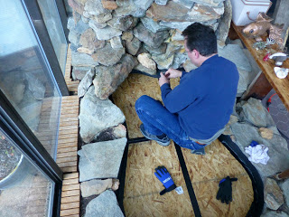 Man applying duct tape to plywood seams in fishpond