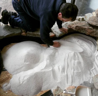 Man spreading sand into small zen garden