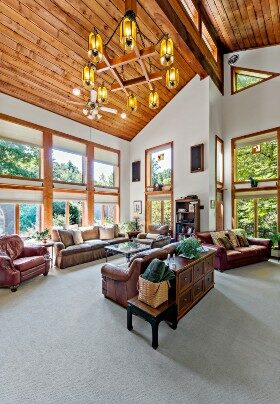 Expansive and bright room with floor to ceiling windows and two-story vaulted wood plank ceiling