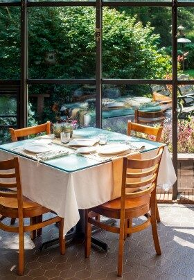Dining table with four chairs and white tablecloth set in a glassed-in solarium with a garden view