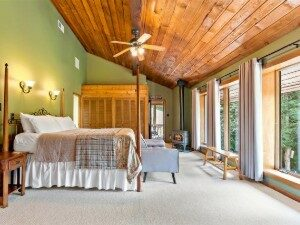 Large bedroom with vaulted cedar plank ceiling, and four poster bed facing wall of floor to ceiling windows