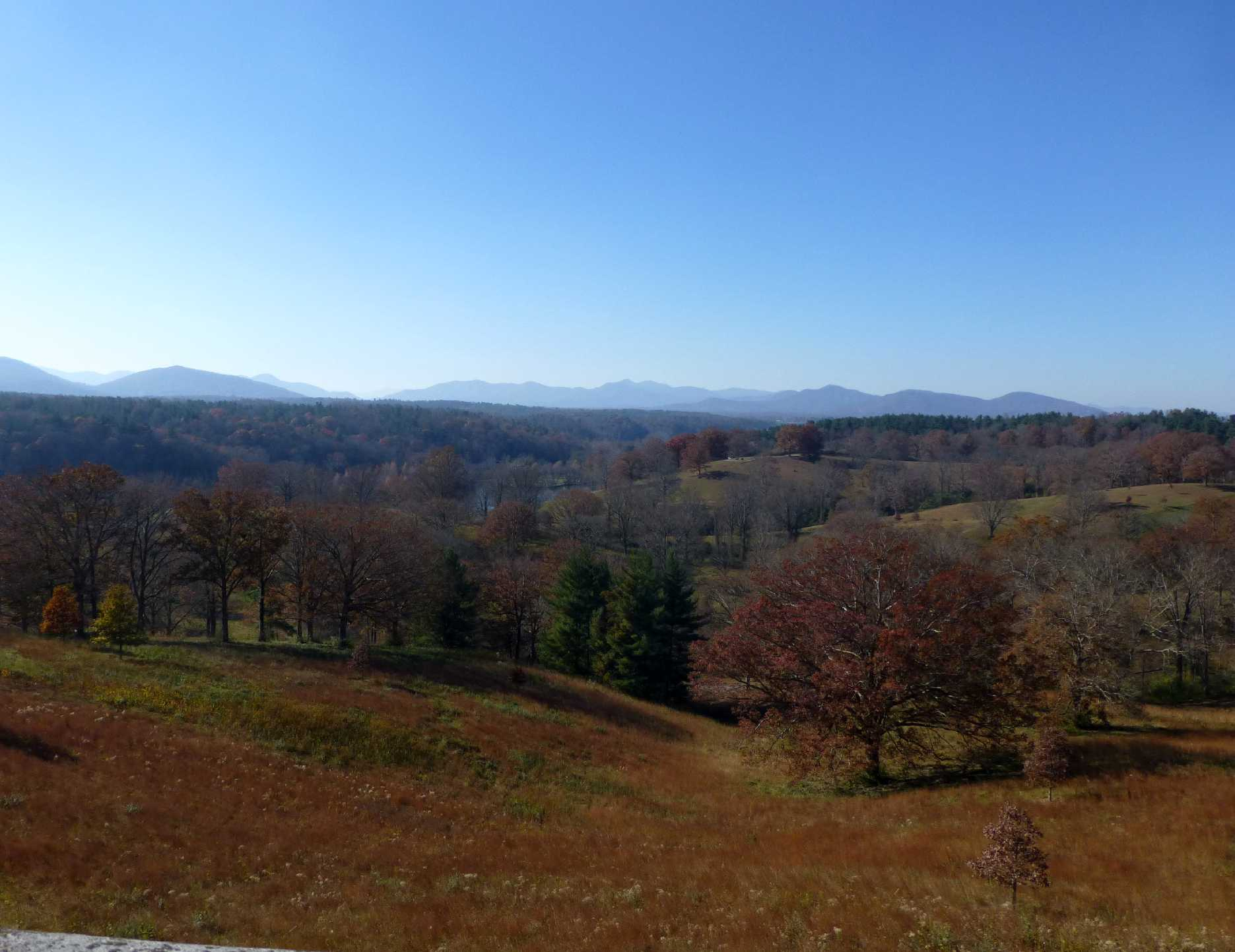 View looking out onto an expansive hilly and wooded landscape with mountains in the distance