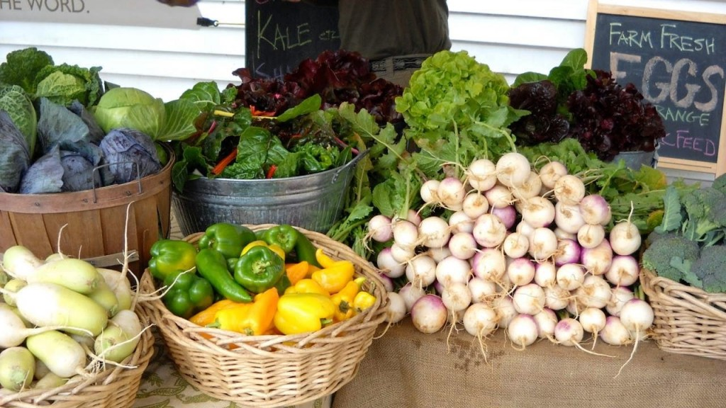 Baskets of peppers and cabbage and other vegetables on a farmers market table