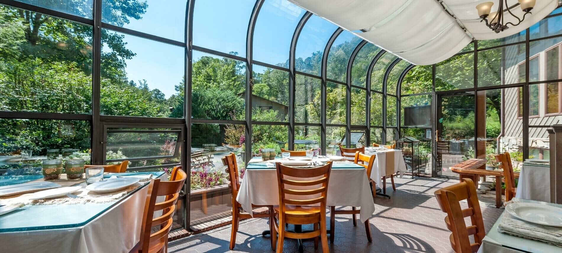 Tables and chairs set for dining in a glassed-in solarium looking out on trees, garden and blue sky
