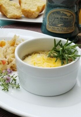 Baked egg dish with cheese and rosemary sprig garnish on plate in front of logo coffee mug and muffins