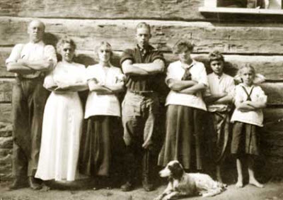 Old family photo of mother and father and five children standing in a row in front of a cabin